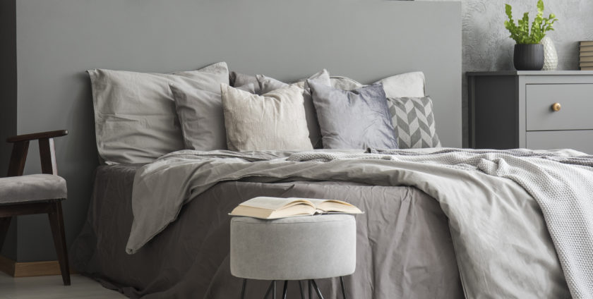 Open book placed on pouf standing next to double bed with grey bedclothes in bedroom interior with armchair and plant on cupboard